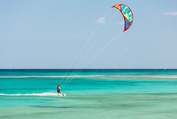 Unknown kitesurfer surfing on a flat azure water of Atlantic ocean in Corralejo, Fuerteventura, Canary islands, Spain