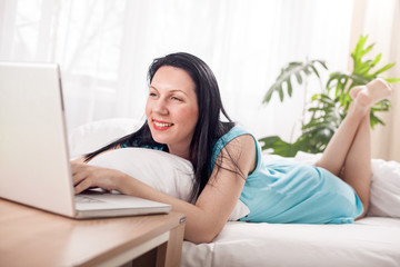 smiling woman using laptop at home in bedroom