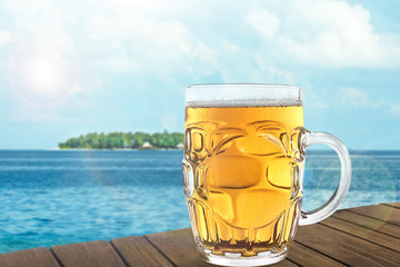Mug of cold fresh beer on table, on sea or ocean background