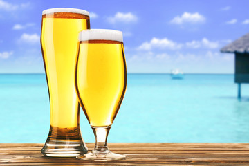 Glasses of cold fresh beer on table, on sea or ocean background