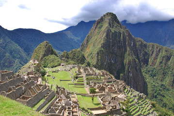 Machu Picchu is located in the Cusco Region of Peru, South America. It is situated on a mountain ridge above the Urubamba Valley in Peru, which is 80 kilometres (50 mi) northwest of Cusco