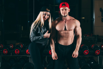 sport, bodybuilding, weightlifting, lifestyle and people concept - Young beautiful couple in stylish clothes sitting a gym near the dumbbells