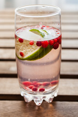 drink from cowberry and a lime in a glass on a table, selective focus