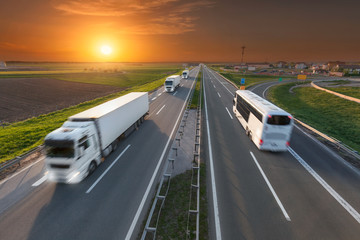 White truck and bus in motion blur on the highway at sunset