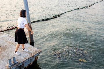 woman student feeding fish at port