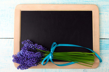 wooden Board for writing with blue Muscari Flowers on a wooden blue background