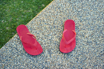 pair of red comfortable slipper placed of stony floor