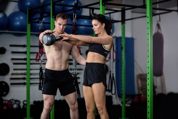 Trainer assisting a woman while exercising with kettlebell
