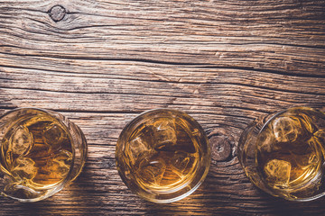 Glasses of whiskey on an old wooden table