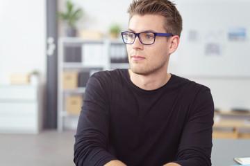 mann im büro schaut nachdenklich zur seite