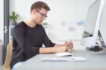 junger geschäftsmann arbeitet konzentriert am schreibtisch