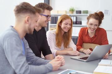 junges team schaut gemeinsam auf laptop