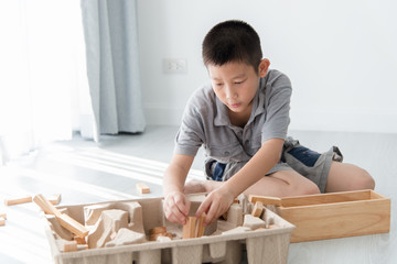 Asian boy playing a Structure from Wooden Building Blocks with b