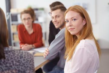 lächelnde, junge frau in einem team-meeting