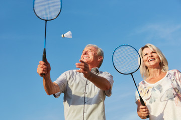 Glückliches Paar Senioren spielt Federball