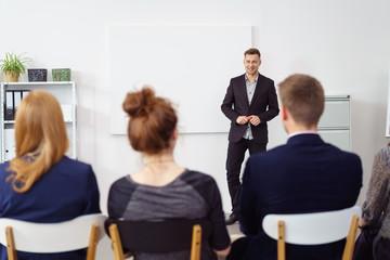 mann steht vor einem jungen team und hält einen vortrag