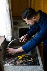 Plumber fixing the sink with wrench