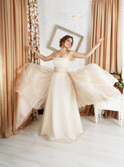 Beautiful young bride in champagne wedding dress