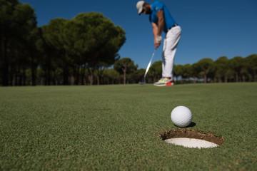 golf player hitting shot, ball on edge of hole