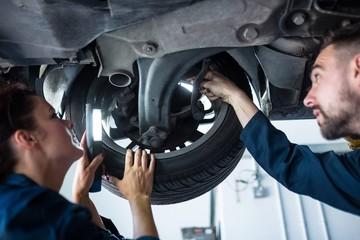 Mechanics examining car tyre using flashlight
