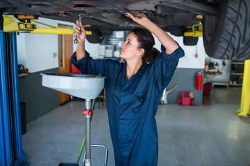 Female mechanic servicing a car