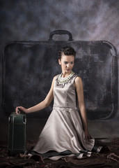 vertical studio image of a model wearing a gray embroidered dress kneeling on the floor next to a suitcase on a gray background and brown velvet material on the floor