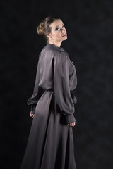 vertical studio image of a young female model in a long black dress with long sleeves on a gray background