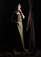 full length vertical artistic studio portrait of a woman wearing a long green dress with neck embroidery on a black background with brown drapery next to her
