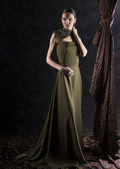 full length vertical studio portrait of a woman wearing a long green dress with neck embroidery on a gray background and brown drapery falling next to and under her