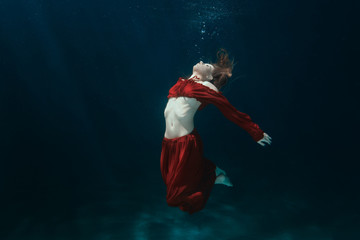 Woman in dress on the bottom underwater.