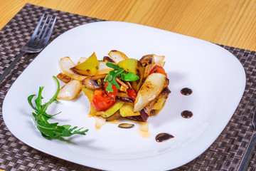 Salad of grilled vegetables on a white plate decorated herbs