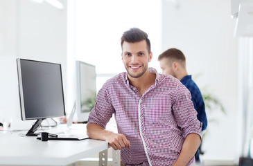 happy creative man with computer at office