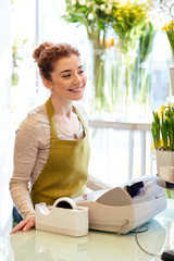 smiling florist woman at flower shop cashbox