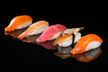 assortment of nigiri sushi on a dark background
