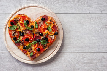 Baked heart-shaped homemade pizza on a cutting board on white wooden background. Close-up
