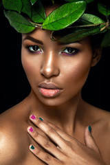 Beautiful woman portrait on black background. Young afro girl posing with green leaves. Gorgeous make up. Pure skin