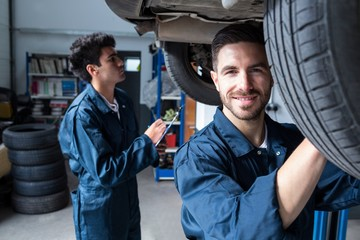 Mechanic fixing a wheel while a colleague preparing a check list