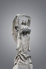 Statue of an angel bearing a palm leaf with a grey background