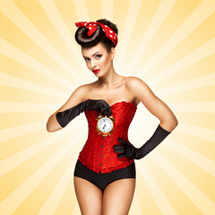Time to bed / Beautiful pinup girl in a red vintage corset being late in the morning and holding a retro alarm clock in her hand on colorful abstract cartoon style background.