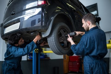 Mechanics fixing a car wheel