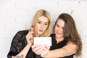 Two women taking a selfie on white wall
