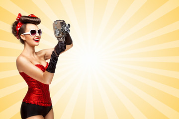 Retro movie style / Retro photo of a glamorous pin-up girl with an old vintage cinema 8 mm camera shooting a movie on colorful abstract cartoon style background.