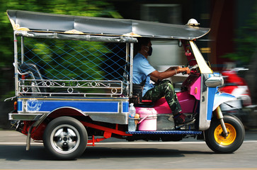 an unidentified man drives Tuk-Tuk in Bangkok