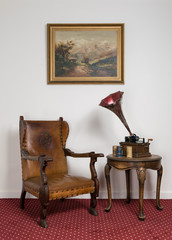 Retro leather armchair, a 1911 old phonograph with three cylinder records on round coffee table and hanged painting on red carpet