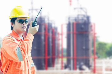 man holding walkie-talkie radio in hand, communication in oil field site