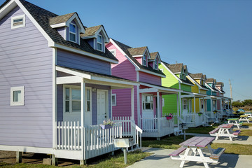 Vibrant colorful houses side by side with picnic tables