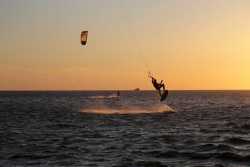Kite surfing with an orange vibrant sunset