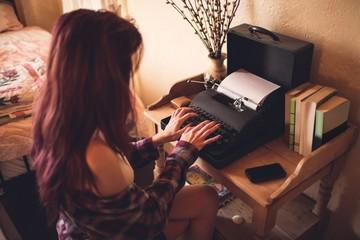 Young woman using typewriter