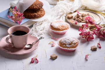 Coffee and sweet desserts, oat biscuits, cupcakes and spring flowers. Still life of breakfast.