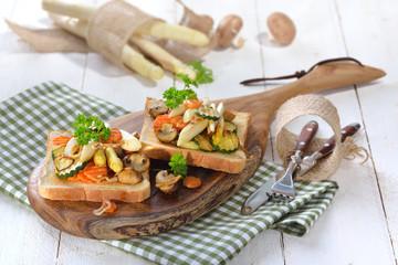 Vegetarischer Toast mit gebratenem weißen Spargel und gemischtem Gemüse, auf einem Holzbrett serviert - Vegetarian toast with fried white asparagus and mixed vegetables, served on a wooden board